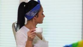 Café da bebida da dona de casa com uma escova da poeira perto das cortinas de janela filme