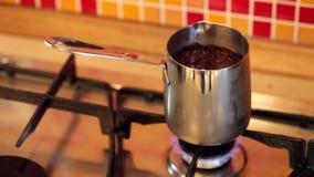Café da fabricação de cerveja no cezve do inox em um fogão de gás filme