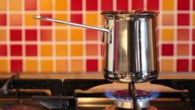 Café da fabricação de cerveja no cezve do inox em um fogão de gás vídeos de arquivo