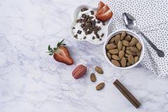 Café da manhã à moda decorado e saudável - morangos, iogurte com granola e amêndoas em um fundo de mármore branco foto de stock