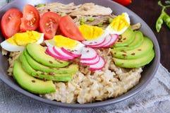 Café da manhã útil: farinha de aveia com carne do coelho, abacate, ovo cozido, tomates, rabanete imagens de stock