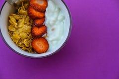 Café da manhã útil: iogurte com morangos e frutos em um purp imagens de stock