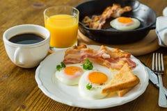 Café da manhã americano com ovos, bacon, brinde, panquecas, café e suco do estrelado Imagens de Stock Royalty Free