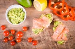 Café da manhã: brinde do abacate com os salmões no fundo de madeira Fotografia de Stock Royalty Free