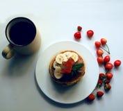 Café da manhã caseiro acolhedor com as panquecas caseiros com banana e cerejas, um copo do chá quente imagens de stock royalty free