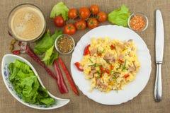 Café da manhã caseiro com uma xícara de café Ovos mexidos frescos com bacon e vegetais Atletas do café da manhã Preparando ovos Imagem de Stock Royalty Free