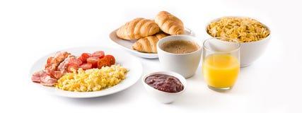 Café da manhã com os flocos dos ovos mexidos, do bacon, dos tomates, do café, do suco de laranja, do croissant e de milho isolado foto de stock royalty free