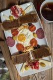 Café da manhã com ovo frito, pão de centeio, romã, pasta da alfarroba, queijos, azeitonas, salame seco, tomates e chá imagens de stock royalty free