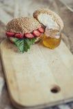 Café da manhã das bagas com um bolo e um mel em uma placa de madeira Foto de Stock Royalty Free