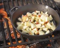 Café da manhã de acampamento - maçãs em uma bandeja do ferro fundido imagens de stock royalty free