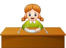 Café da manhã de espera dos desenhos animados bonitos da menina na mesa de jantar Foto de Stock Royalty Free