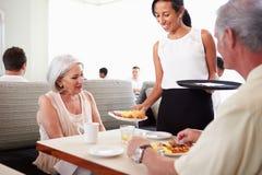 Café da manhã de Serving Senior Couple da empregada de mesa no restaurante do hotel imagem de stock royalty free
