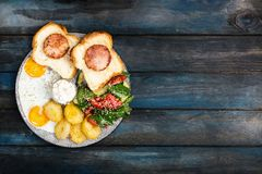 Café da manhã delicioso grande com ovos fritos, as batatas fritadas, salada fresca, presunto da galinha no pão e molho de creme V foto de stock