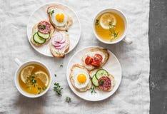 Café da manhã delicioso - mini sanduíches com queijo creme, vegetais, ovos de codorniz, salame e chá verde com limão e tomilho Sa foto de stock royalty free