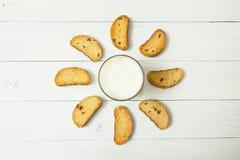 Café da manhã dietético, iogurte ácido em um copo de vidro e biscoitos com passas em uma tabela branca na forma do sol imagem de stock royalty free