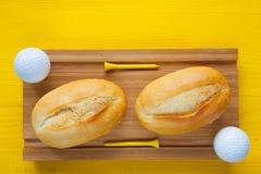 Café da manhã do golfe - duas pão integral e bolas de golfe Fotografia de Stock Royalty Free