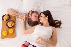Café da manhã do homem e da mulher na cama foto de stock