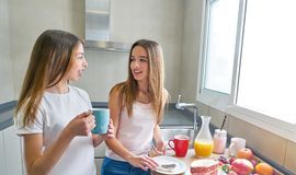 Café da manhã dos adolescentes das meninas dos melhores amigos na cozinha Fotografia de Stock Royalty Free