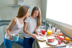 Café da manhã dos adolescentes das meninas dos melhores amigos na cozinha Imagens de Stock