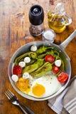 Café da manhã em uma frigideira ovos fritos com salada pe verde fritado Fotos de Stock Royalty Free