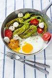 Café da manhã em uma frigideira ovos fritos com salada pe verde fritado Fotografia de Stock Royalty Free