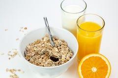 Café da manhã equilibrado com bacia do muesli, leite e suco de laranja fresco foto de stock