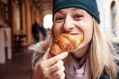 Café da manhã exterior da barra do croissant da mordida da mulher Imagem de Stock Royalty Free