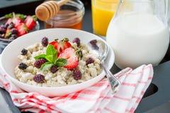 Café da manhã - farinha de aveia com mel e bagas, bacia azul Foto de Stock