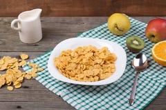Café da manhã: flocos em uma placa, leite em um jarro Fotos de Stock Royalty Free