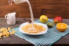 Café da manhã: flocos em uma placa, leite em um jarro Fotografia de Stock