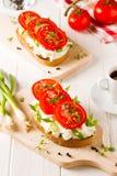 Café da manhã fresco da mola com pão brindado com queijo e tomates Fotografia de Stock