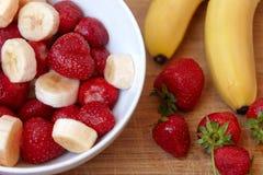 Café da manhã, morango e bananas saudáveis da refeição Conceito natural orgânico da dieta, placa branca na mesa de madeira fotografia de stock