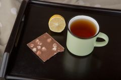 Caf? da manh? na cama - copo do ch?, do lim?o e do chocolate na bandeja de madeira imagem de stock