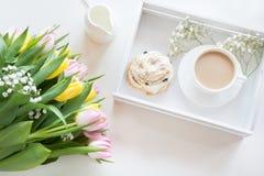 Café da manhã da manhã na mola com um copo do café preto com leite e pastelarias nas cores pastel, um ramalhete de amarelo fresco Foto de Stock Royalty Free