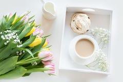 Café da manhã da manhã na mola com um copo do café preto com leite e pastelarias nas cores pastel, um ramalhete de amarelo fresco Imagem de Stock Royalty Free