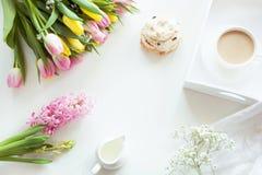 Café da manhã da manhã na mola com um copo do café preto com leite e pastelarias nas cores pastel, um ramalhete de amarelo fresco Fotografia de Stock Royalty Free