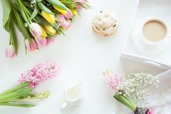 Café da manhã da manhã na mola com um copo do café preto com leite e pastelarias nas cores pastel, um ramalhete de amarelo fresco Fotografia de Stock