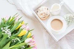 Café da manhã da manhã na mola com um copo do café preto com leite e pastelarias nas cores pastel, um ramalhete de amarelo fresco Fotos de Stock