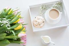 Café da manhã da manhã na mola com um copo do café preto com leite e pastelarias nas cores pastel, um ramalhete de amarelo fresco Imagem de Stock