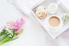 Café da manhã da manhã na mola com um copo do café preto com leite e pastelarias nas cores pastel, um ramalhete do hyacin cor-de- Fotos de Stock