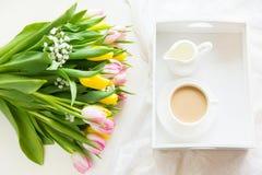Café da manhã da manhã na mola com um copo do café preto com leite nas cores pastel, um ramalhete das tulipas amarelas e cor-de-r Fotografia de Stock Royalty Free
