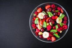 Café da manhã natural, salada de fruto na placa de vidro na tabela preta Configuração lisa, vista superior foto de stock