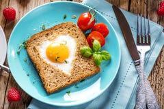 Café da manhã no dia de Valentim - ovos fritos e pão na forma de um coração e de uns legumes frescos imagem de stock royalty free
