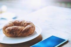 Café da manhã no escritório com croissant e o telefone esperto foto de stock royalty free