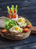 Café da manhã ou petisco delicioso - sanduíche com queijo e um ovo de codorniz fritado, um iogurte grego, um aipo e umas pimentas Imagens de Stock Royalty Free