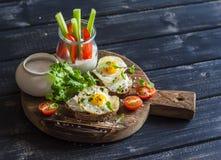 Café da manhã ou petisco delicioso saudável - sanduíche com queijo e um ovo de codorniz fritado, um iogurte grego, um aipo e umas Foto de Stock