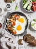 Café da manhã ou petisco delicioso - um ovo frito, feijões no molho de tomate com cebolas e cenouras, pepinos frescos e tomates,  Imagem de Stock Royalty Free