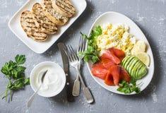 Café da manhã ou petisco equilibrado saudável - salmão fumado, salada do ovo e abacate Em um fundo cinzento, vista superior Alime imagens de stock