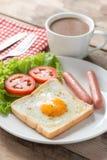 Café da manhã, ovo em um furo com salsicha e café Imagem de Stock