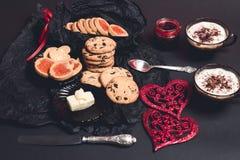 Café da manhã romântico duas xícaras de café, cappuccino com cookies do chocolate e biscoitos perto dos corações vermelhos no fun Fotografia de Stock Royalty Free